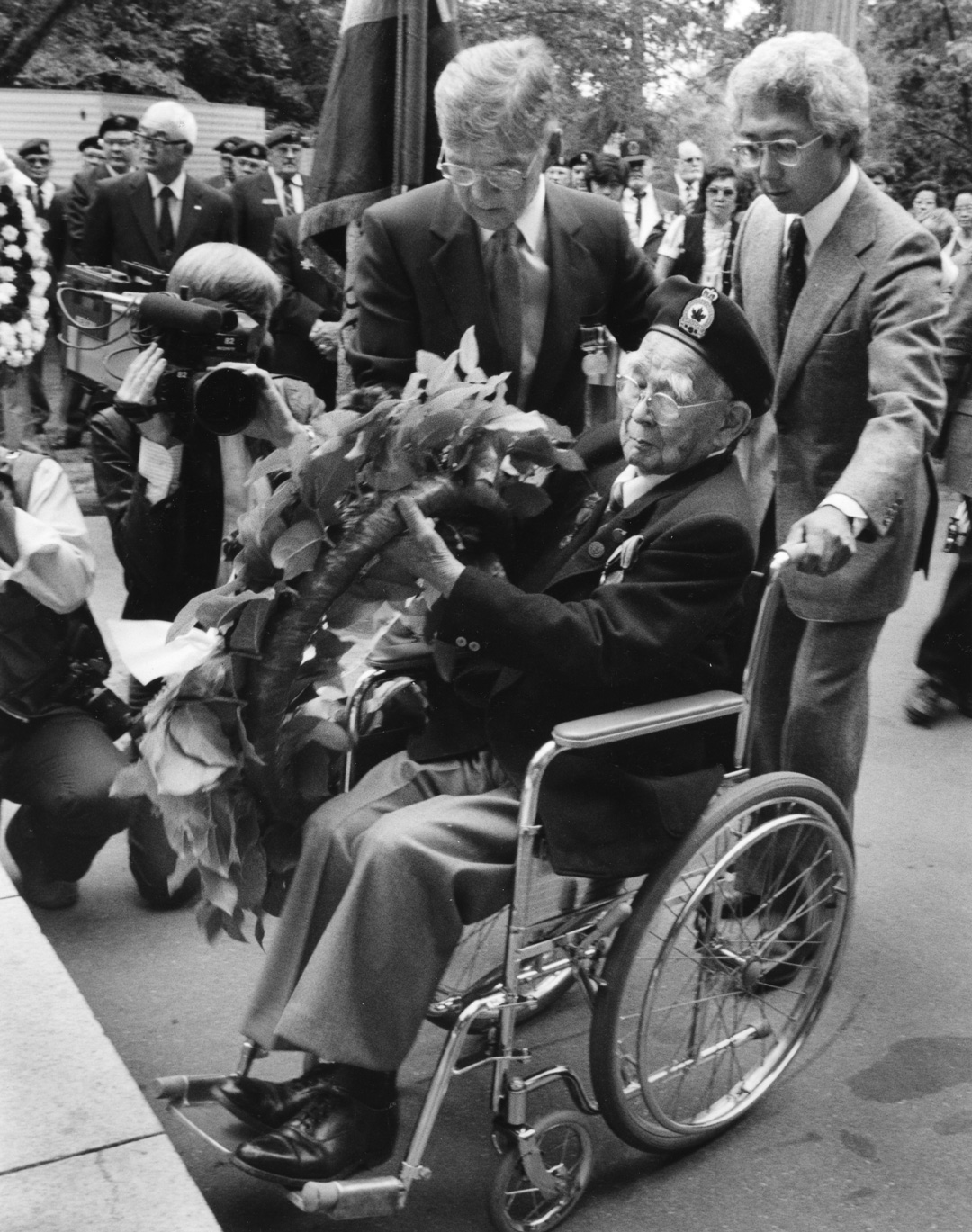 Sergeant Mitsui (seated, in wheelchair) placing a wreath at the Japanese Canadian War Memorial in Stanley Park, 1985. NNM 1992.23