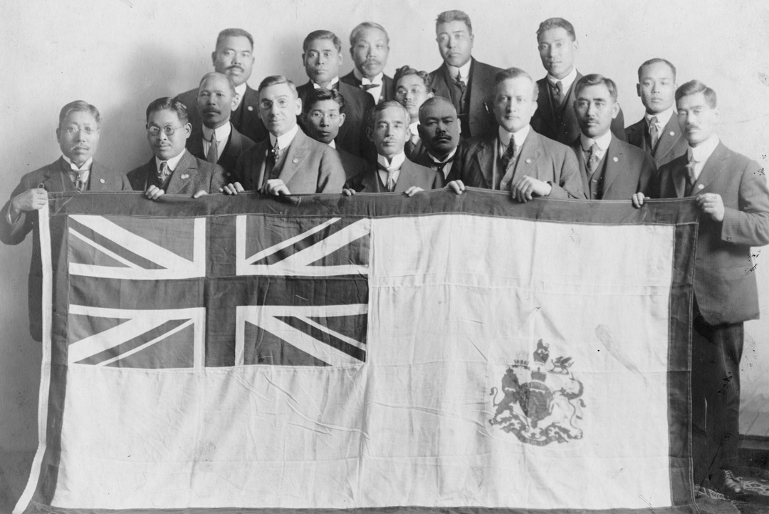 Commemorative photograph taken at the end of the war, circa 1918. Matsunoshin Abe, the president of the Canadian Japanese Association at the time, is the man on the far left, and Saburo Shinobu is on the far right. Consul General Satotsuga Ukita, who was in office 1916-1921, is in the centre of the front row (fourth from the left holding the flag). NNM 1994.70.27