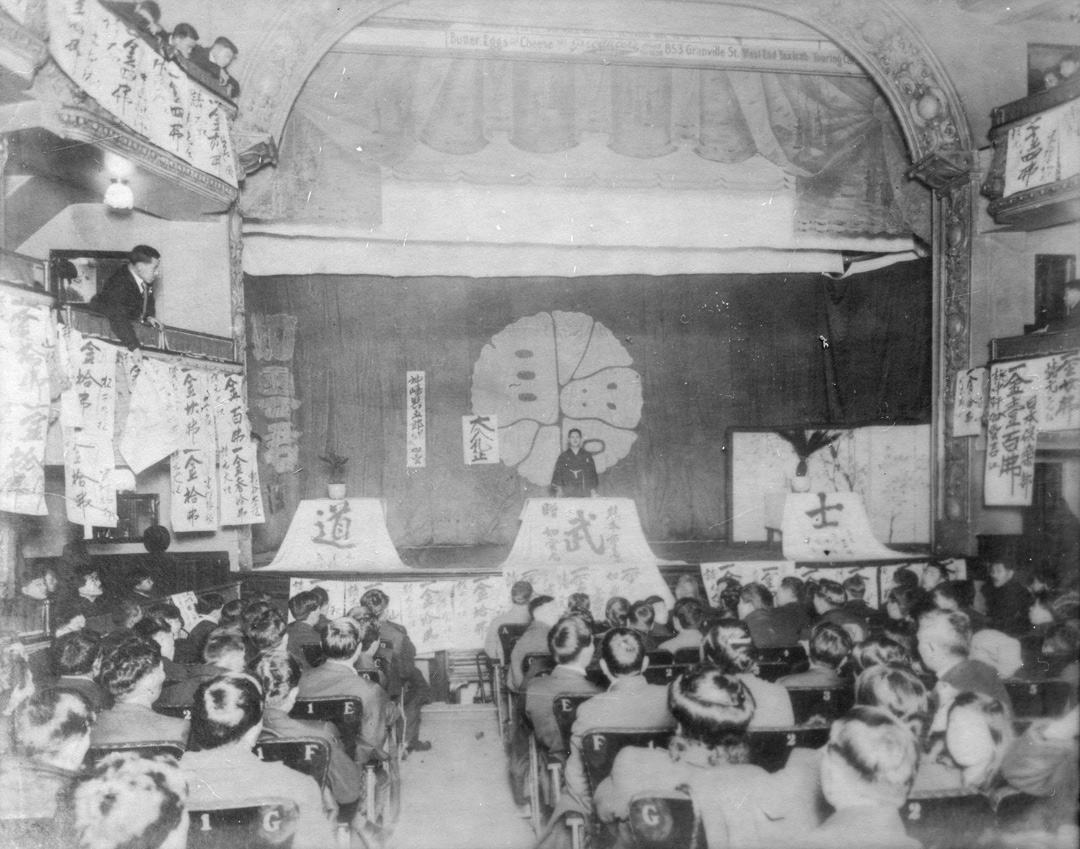 "Community fundraising event, circa 1908. The Japanese characters on the panels at the front of the stage read ""bushido"", a word for the samurai code of values. Japanese Canadian Cultural Centre 2001.15.4"